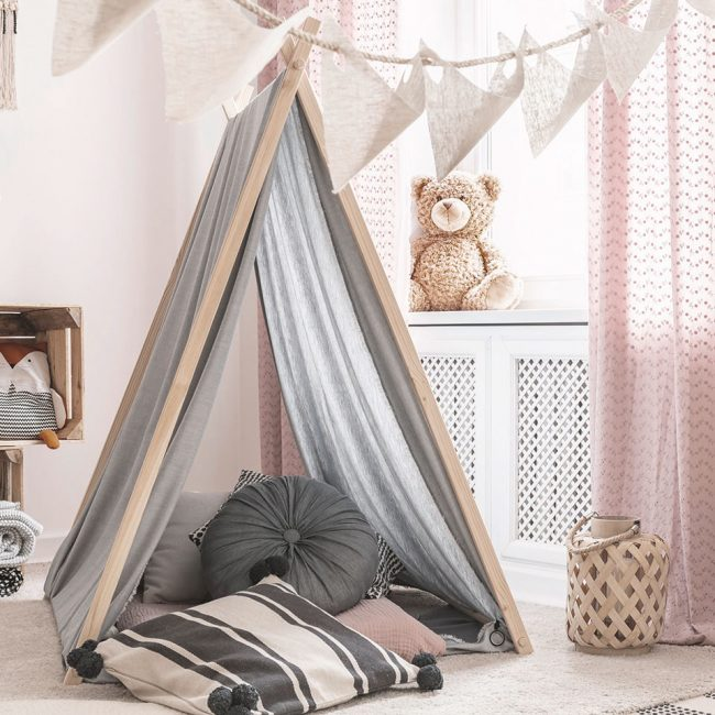 Pillows in patterned tent in kid's room interior with lamp on wo